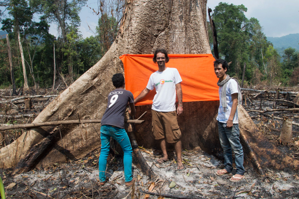 Mother Nature founder Alex Gonzalez-Davidson (center) stands in front of a tree that has been blessed by monks in Tatai Leur commune in the Areng Valley of Cambodia's Cardamom Mountains, in November 2013. Since Gonzalez-Davidson's deportation from Cambodia in February, Tim Malay (right), President of the Cambodian Youth Network, has continued to support Mother Nature's campaign to save the Areng Valley. Photo by: Rod Harbinson.