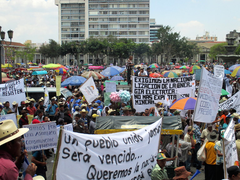 A crowd gathers at a May 20 march and rally in Guatemala City over recent revelations of widespread government corruption. One of the banners calls for the nationalization of electrical energy and a halt to mining. Photo by Sandra Cuffe.
