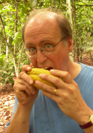 Dr. Tom Neuhaus bites directly out of a freshly opened cocoa pod.