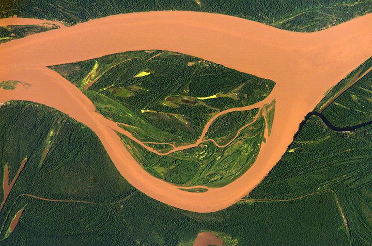 "Amazon River aerial photo on the Peru-Colombia frontier, clearly showing the stream's heavy load of ""brown-river"" sediment. Photo courtesy of NASA"
