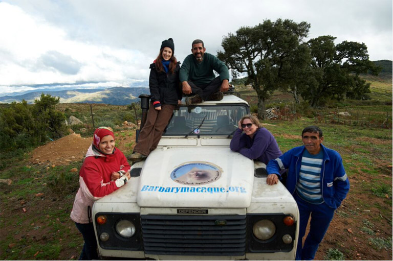 (From left to right) Kenza, Lucy, Ahmed, Sian and Mohamed gather around the Monkey Bus for a group photo at the site of the conservation and education centre, with mountains shrouded by cloud in the background. Photo credit: Andrew Walmsley.