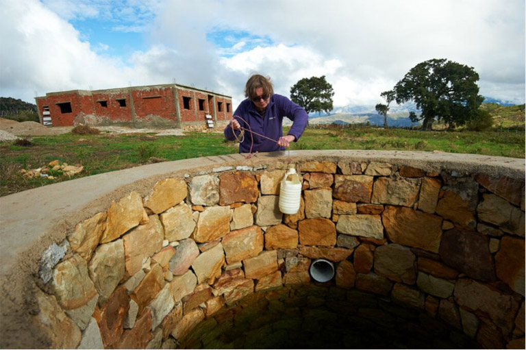 Sian draws water from the newly-constructed well at the site of the almost-completed conservation and education centre. Photo credit: Andrew Walmsley.
