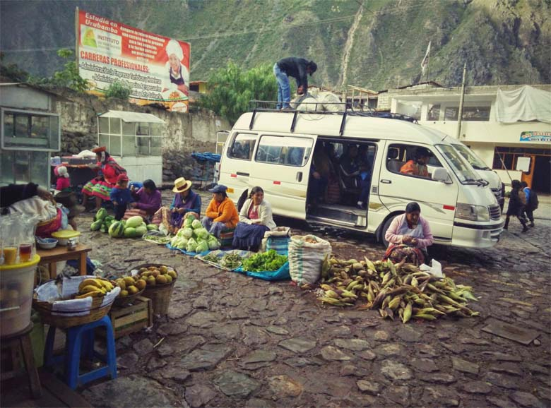 A 'combi' van unloads at a small market in Ollantaytambo, site of the nearest paved road — and market — to Patacancha. The vans are workhorses of Peruvian village life, carrying passengers and goods to and from market. Campesinos subject the vans to staggering loads. On my way up to Yupanqui's village, the van carried half a ton of plaster; on the way down, we took a ton of a corn. All male passengers, and some female, helped unload. Credit: Saul Elbein