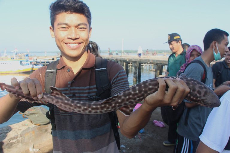 A student from Lombok's University of Mataram displays a specimen from his class field trip to Tanjung Luar port, Lombok. The trip is an annual event for professor Khairuddin (shown wearing a cap in background). The fish will be taken back to the university lab to be classified. Photo credit: Melati Kaye.