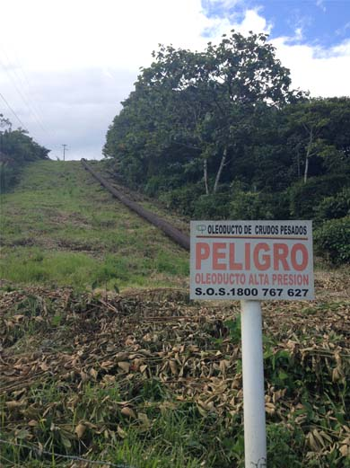 Danger sign warns people away from oil pipeline on the road to Sucumbios. Photo credit: Veronica Goyzueta.