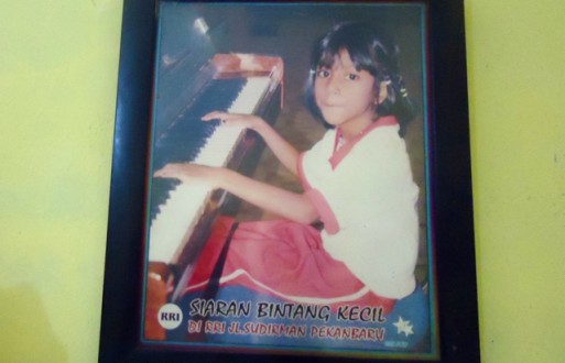 A picture of Hanum playing the piano hangs on the wall of her family's house. Photo by Made Ali