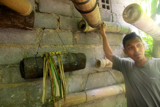 Thirty-three-year-old farmer Durpa Adnyana with his beehives. Photo by Anton Muhajir