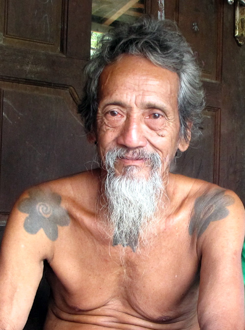 """Eighty-four-year-old Bandi, known as Apay Janggut, or """"the bearded one,"""" sits in a longhouse in Indonesian Borneo. Photo by Andi Fachrizal"""