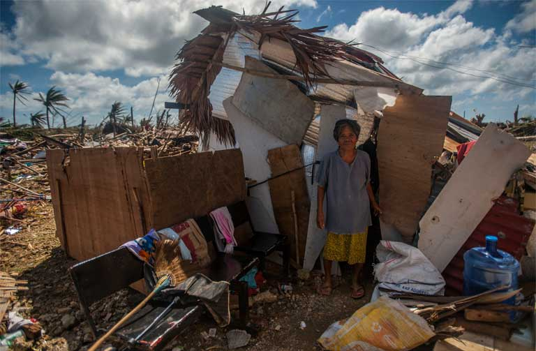 "Super Typhoon Haiyan, November 15, 2013, the Philippines. A woman stands outside her makeshift shack in the storm's aftermath. We ""must integrate questions of justice in debates on the environment, so as to hear the cry of the earth and the cry of the poor,"" wrote Pope Francis in his encyclical. Photo by Mass Communication Specialist Seaman Liam Kennedy courtesy of the U.S. Navy."