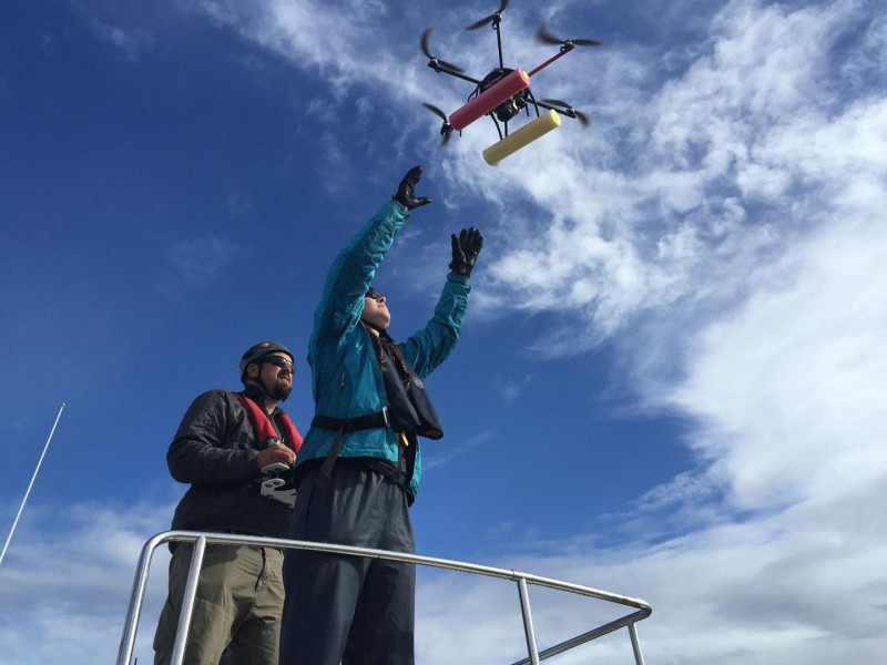Dr. John Durban is piloting the hexacopter into the hands of co-pilot Dr. Holly Fearnbach. The biologists, both with NOAA's Southwest Fisheries Science Center, are using the hexacopter to capture images of killer whales in order to assess their health. Photo credit: NOAA Fisheries.