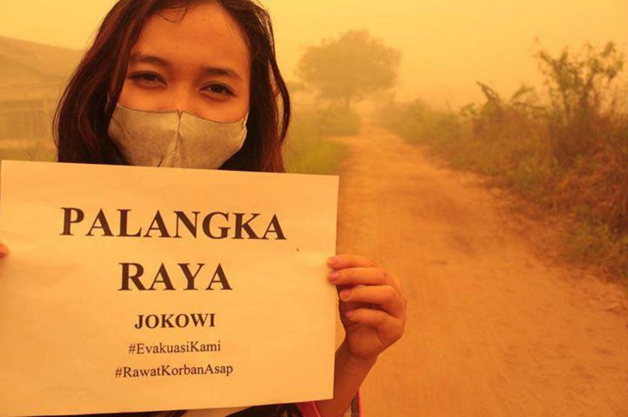A girl in Palangkaraya, the capital of Central Kalimantan, holds up a sign asking President Jokowi to evacuate area residents from the haze-hit region. Much of Sumatra and Kalimantan have been submerged in toxic smoke from out-of-control wildfires and underground hotspots as a result of unchecked land clearing for agriculture and the year's extended dry season due to El Niño. Photo courtesy of the @twt_marathon Twitter account.