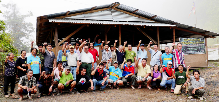 Protesters pose in front of a building at a blockade camp at kilometer 15 of the Baram Dam access road. Protesters have been blockading work at the site of the proposed dam for two years, arguing that the dam would threaten local indigenous peoples' way of life. The Sarawak government placed a moratorium on the project this summer. Photo courtesy of SAVE Rivers Sarawak.