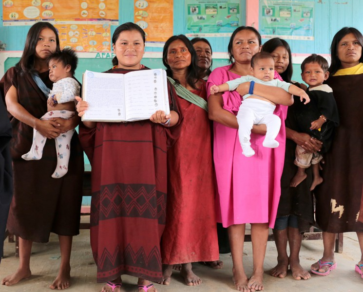 Members of the Saweto community display the title granting them rights to 81,000 hectares of their land. Photo courtesy of the Rainforest Foundation.
