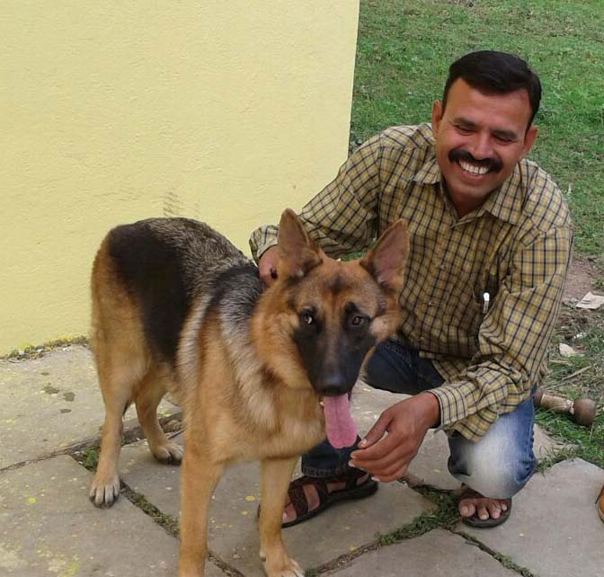 TRAFFIC's sniffer dog Myna with her handler Dinesh Anjana. The team graduated in June and busted a pair of illegal wildlife traders their first day on the job. Photo courtesy of TRAFFIC India.