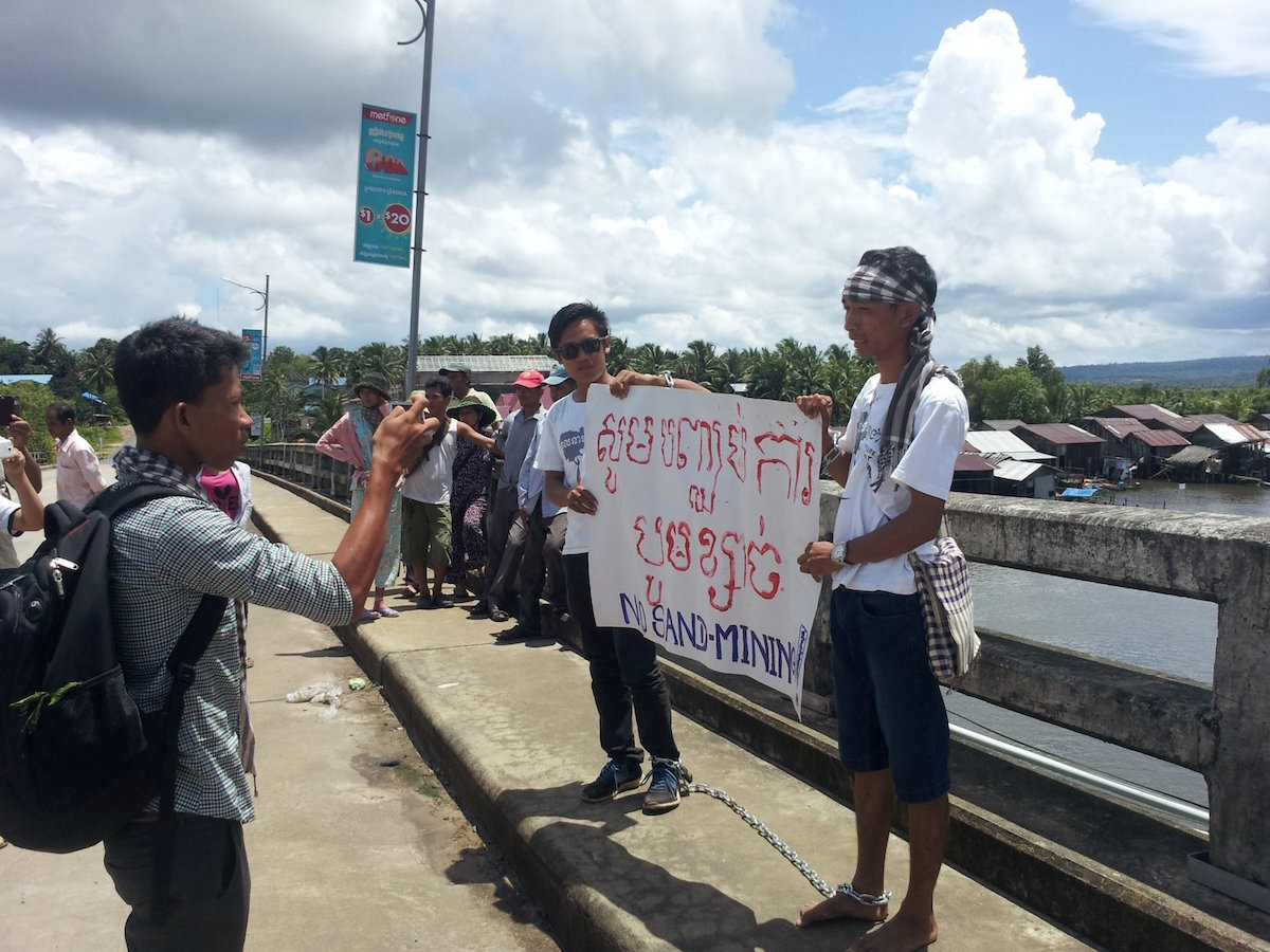 After receiving a summons from police, Try Sovikea (left) and San Mala (right) await arrest on a bridge over the over the Andong Teuk River on August 15. Photo courtesy of Mother Nature Cambodia.