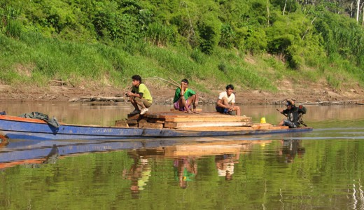 Boat loaded with wood on the Tambopata River, Peru