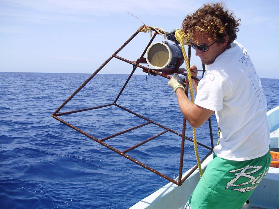 Mark Bond, a researcher with Global FinPrint and Stony Brook University, positions one of the baited remove underwater video (BRUV) cameras at Glover's Reef Marine Reserve. Copyright Global Finprint.