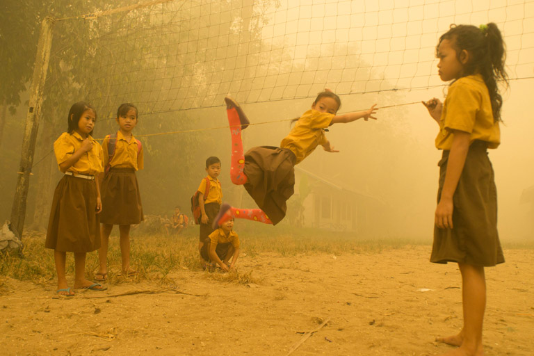 Children enjoy playing without wearing any protection at the playground while the air is engulfed with thick haze from the forest fires at Sei Ahass village, Kapuas district in Central Kalimantan province on Borneo island, Indonesia. These fires are a threat to the health of millions. Smoke from landscape fires kills an estimated 110,000 people every year across Southeast Asia, mostly as a result of heart and lung problems, and weakening newborn babies.