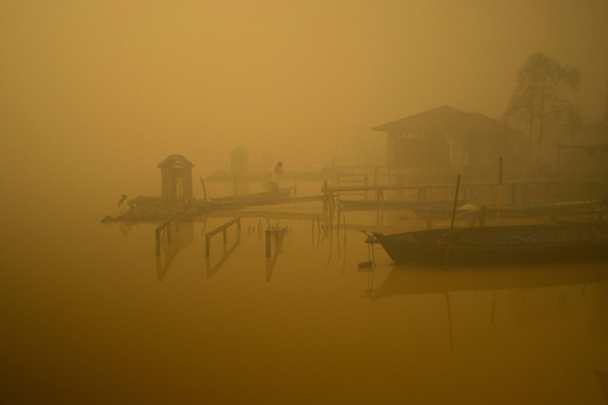 Members of the indigenous community live at the riverbanks in Kapuas river where the air is engulfed with thick haze at Sei Ahass village, Kapuas district, Central Kalimantan province on Borneo island, Indonesia. These fires are a threat to the health of millions.
