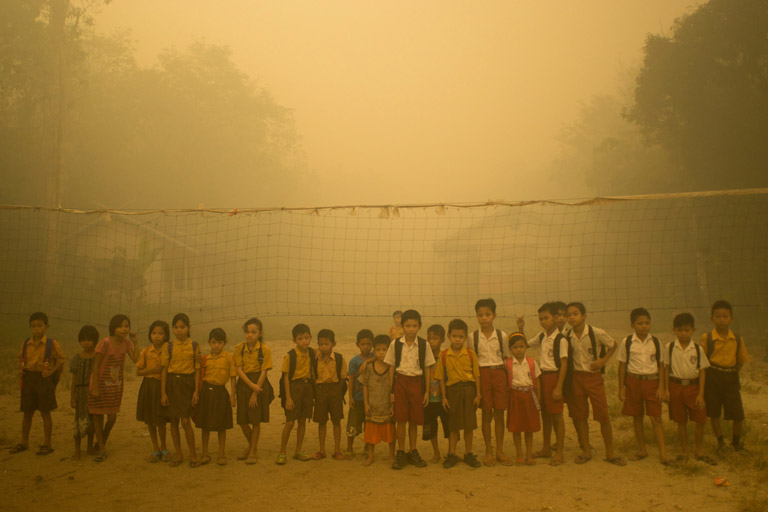 Children play without wearing any protection at the playground while the air is engulfed with thick haze from the forest fires at Sei Ahass village, Kapuas district in Central Kalimantan province on Borneo island, Indonesia. These fires are a threat to the health of millions. Smoke from landscape fires kills an estimated 110,000 people every year across Southeast Asia, mostly as a result of heart and lung problems, and weakening newborn babies.
