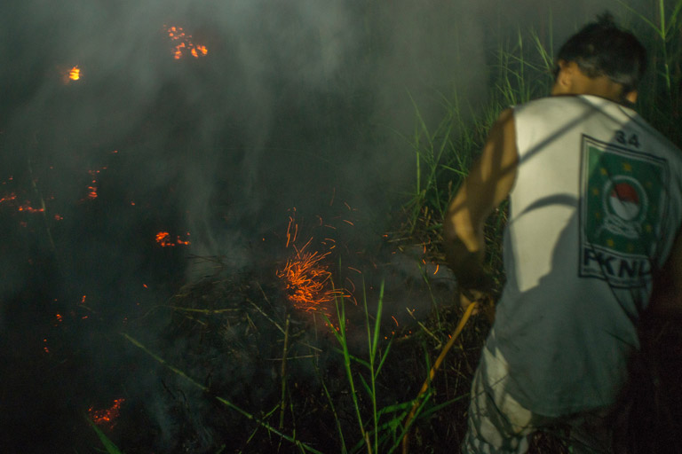 Members of the local community help extinguish the fire of a burning peatland in Kapuas district, Central Kalimantan province on Borneo island, Indonesia.