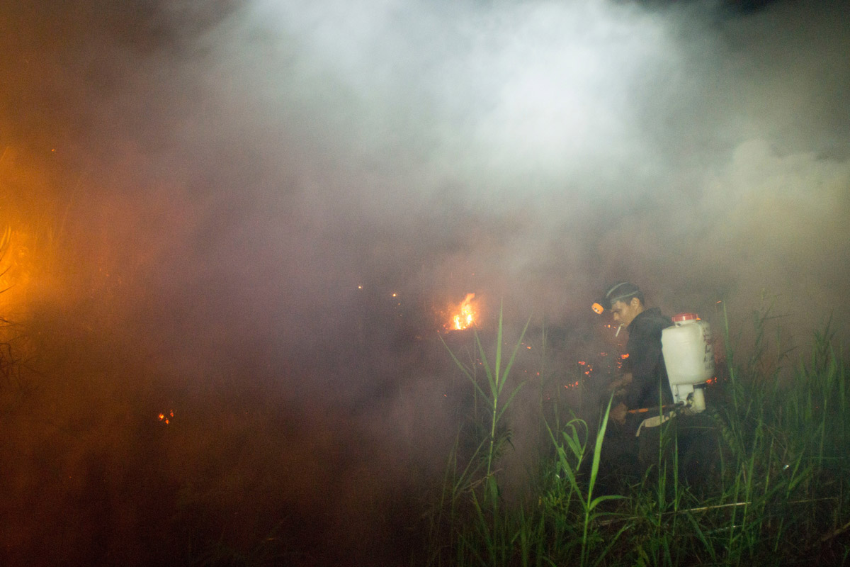 Members of the local community help extinguish the fire of burning peatland in Kapuas district, Central Kalimantan province on Borneo island, Indonesia.