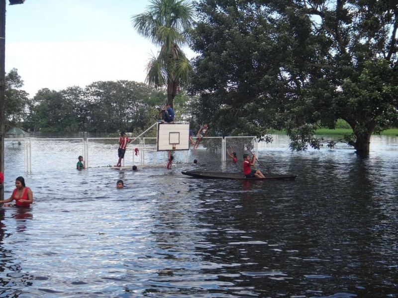 Children playing in the water on the basketball court flooded by the Amazon, in the lower part of Puerto Nariño. Photo by Elvira Durán.