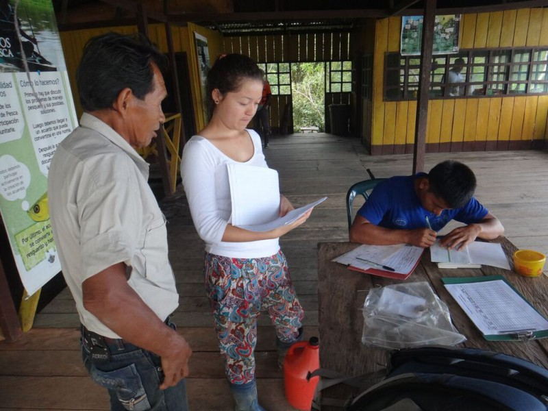 Lisette Johanna Escobar checking paperwork with the fishermen on the monitoring houseboat on Lake Tarapoto. Photo by Elvira Durán.
