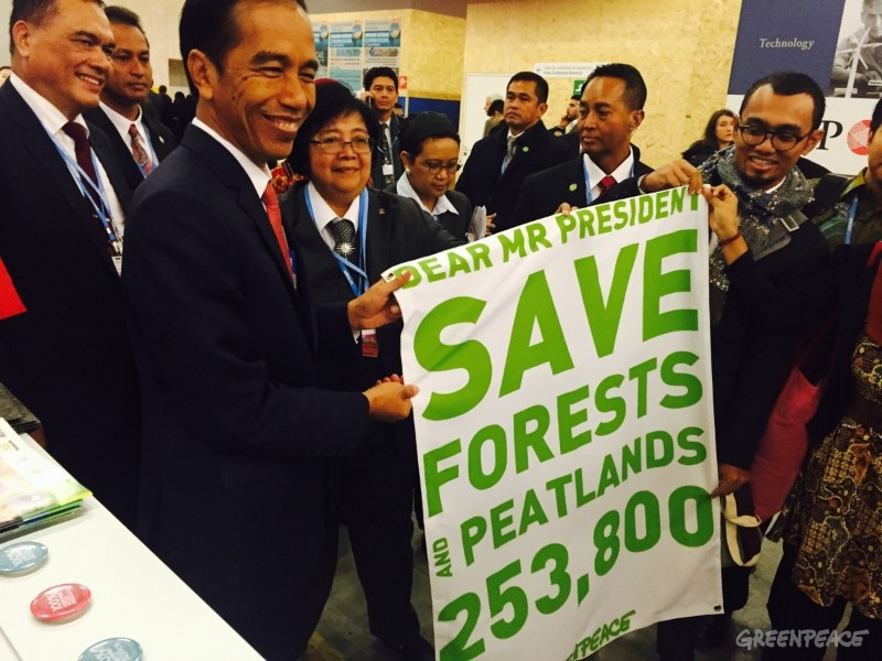 President Jokowi holds a banner referencing the support of 253,800 people for saving Indonesia's forests and peatlands at the climate talks in Paris on Monday. Photo courtesy of Greenpeace