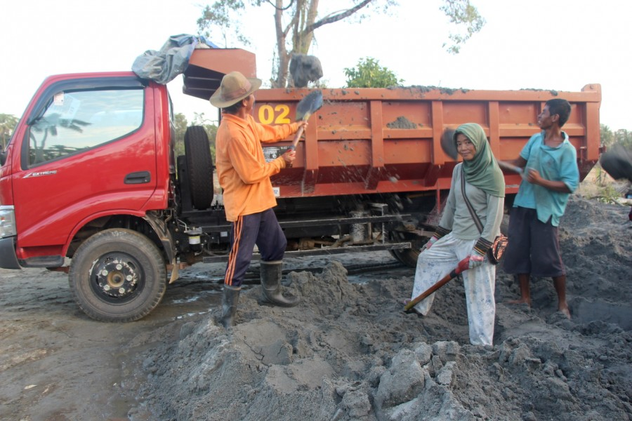 Purui villager Tina loading fine grain sand into a lorry bound for Kendari, Southeast Sulawesi. Photo by Melati Kaye