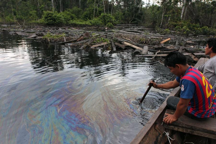 CUNINICO, Peru–Villager examine oil slick near this Kukama Indian village in the northeastern Peruvian Amazon. Photo by Barbara Fraser.