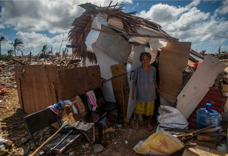 Super Typhoon Haiyan, November 15, 2013, the Philippines. A woman stands outside her makeshift shack in the storm's aftermath. The world's poor are the hardest hit by climate change. Photo by Mass Communication Specialist Seaman Liam Kennedy courtesy of the U.S. Navy.