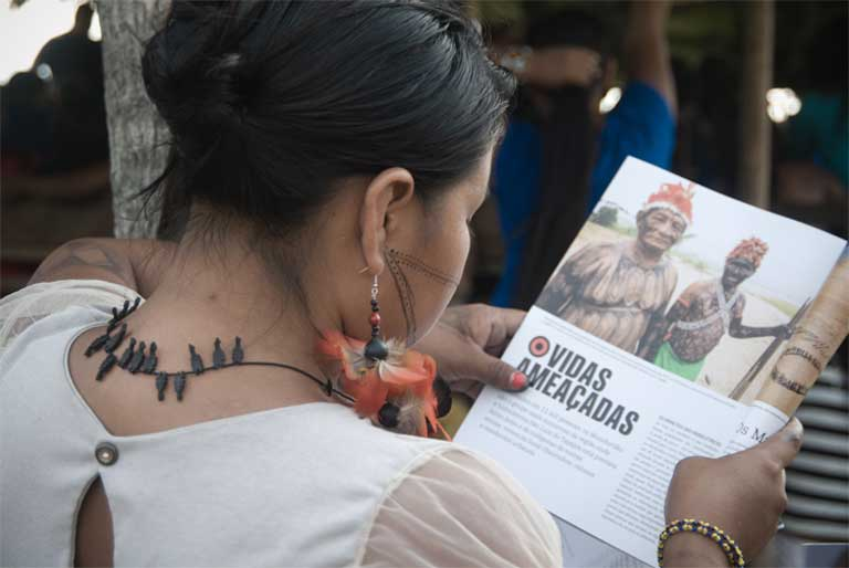 A Munduruku woman reads an article about dam-related conflicts during the meeting. Photo by Anderson Barbosa of the Anderson Barbosa / Fractures Collective