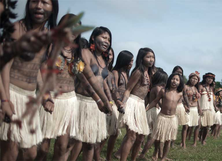 Munduruku women gather in a circle and dance, performing a traditional ritual during a 2013 assembly in Restinga village. The indigenous group has maintained its culture and autonomy despite past attempts by Christian missionaries to ban their language and rites. Group leaders fear that the new dams would do significant cultural and economic harm. Photo by Anderson Barbosa of the Anderson Barbosa / Fractures Collective