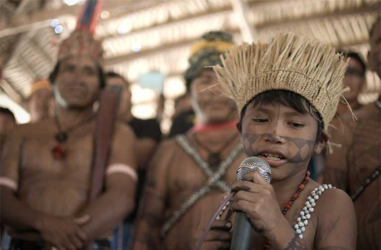 A Munduruku boy sings during the welcoming reception for the Tapajós assembly participants in Dace Watpu village, September 2015. The village would be flooded by the largest of the new Tapajós dams. Photo by Anderson Barbosa of the Anderson Barbosa / Fractures Collective