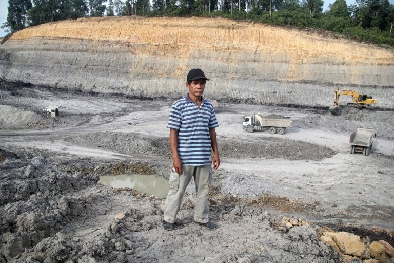 A man in Indonesia's West Kutai district stands in front of a coal mine whose operator he says encroached on his land. West Kutai is next to Kutai Kartanegara. Photo by Philip Jacobson