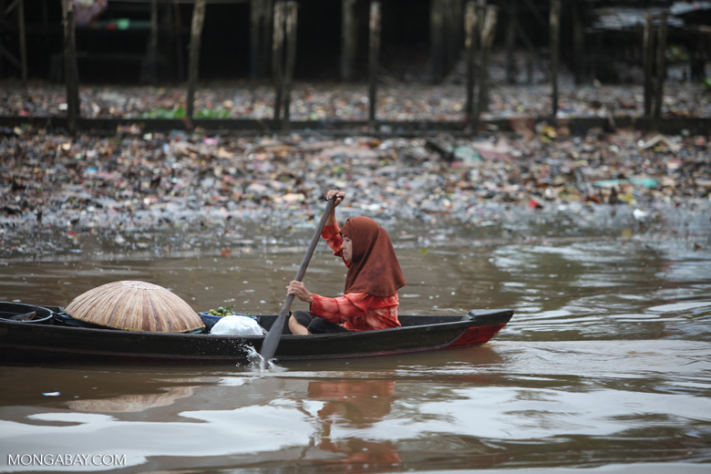 Woman paddling in a canoe along a trash-lined river in Banjarmasin, Indonesia. Photo by Rhett Butler.