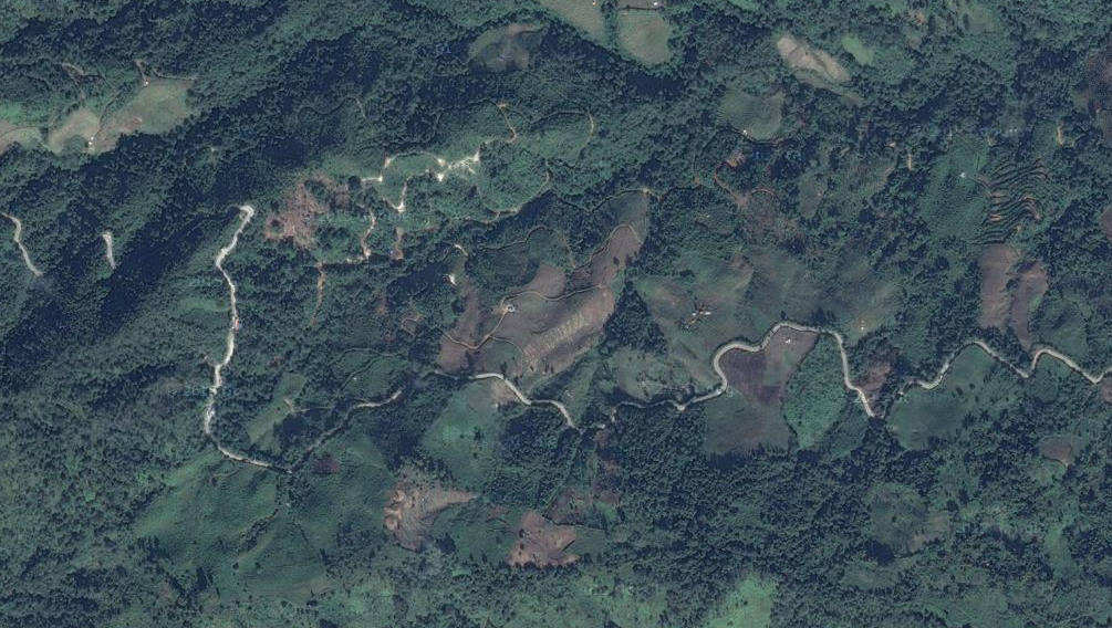 A road in Myanmar winds through once-forest near the Chinese border.