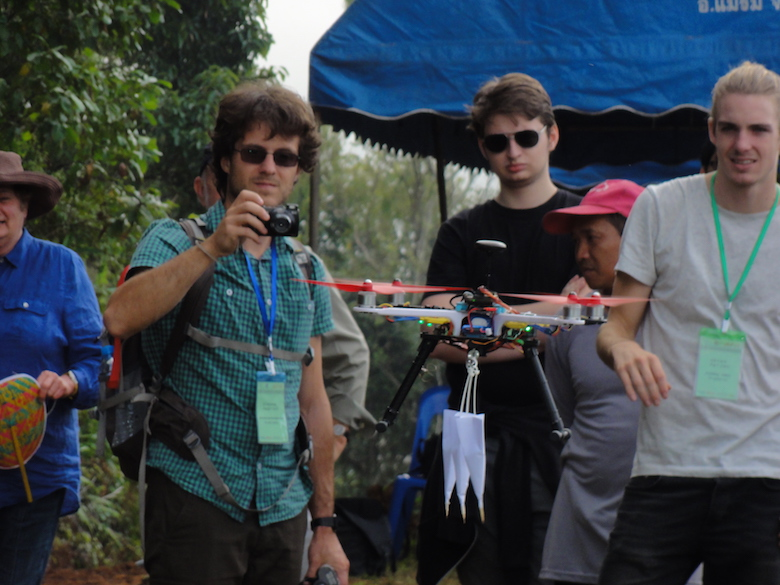 Onlookers watch a demonstration of a seed-dispersing drone, which can drop darts containing seeds. The demonstration took place during a workshop on automated forest restoration this fall in Thailand. Photo by S. Elliott.