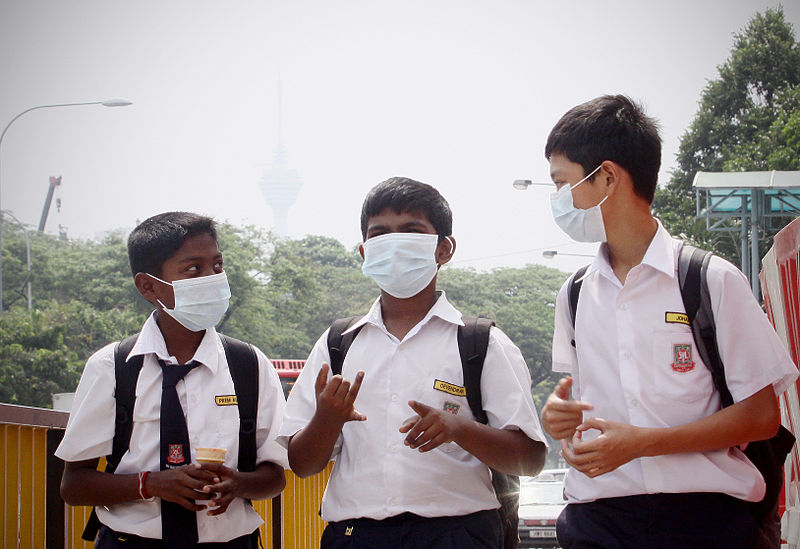Malaysian schoolboys wear facemasks with Kuala Lumpur affected by haze pollution in 2012. Photo by Firdaus Latif/Wikimedia Commons