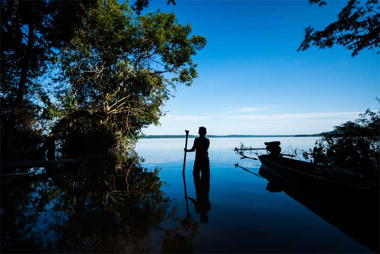 A member of the Munduruku indigenous group stands beside the Tapajós River, Pará state, Brazil. The Munduruku's Sawré Muybu territory on the Tapajós is threatened by a proposed dam complex including the São Luiz do Tapajós dam. Those territorial claims were recently recognised by the Brazilian government, putting the licensing of the dam in doubt. Photo © Valdemir Cunha / Greenpeace
