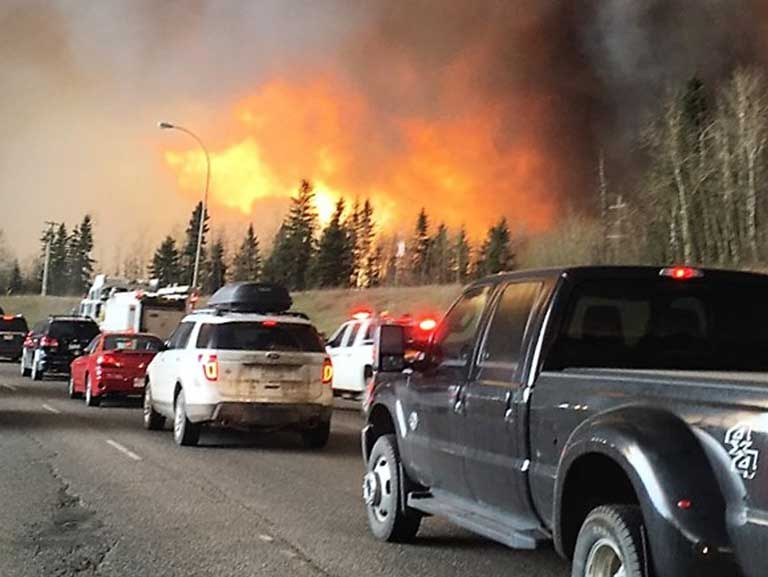 Industrialized world climate refugees: Fort Mcmurray residents flee the wildfires that have burned more than 20 percent of this Canadian community. Photo by DarrenRD licensed under the Creative-Commons Attribution Share-Alike 4.0 International license