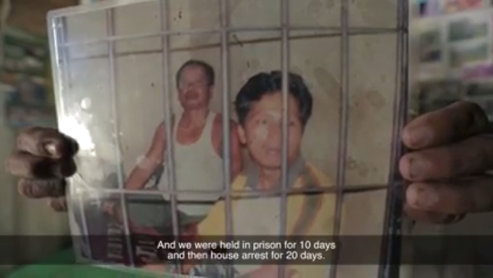 Momonus holds a photo from when he was in prison.
