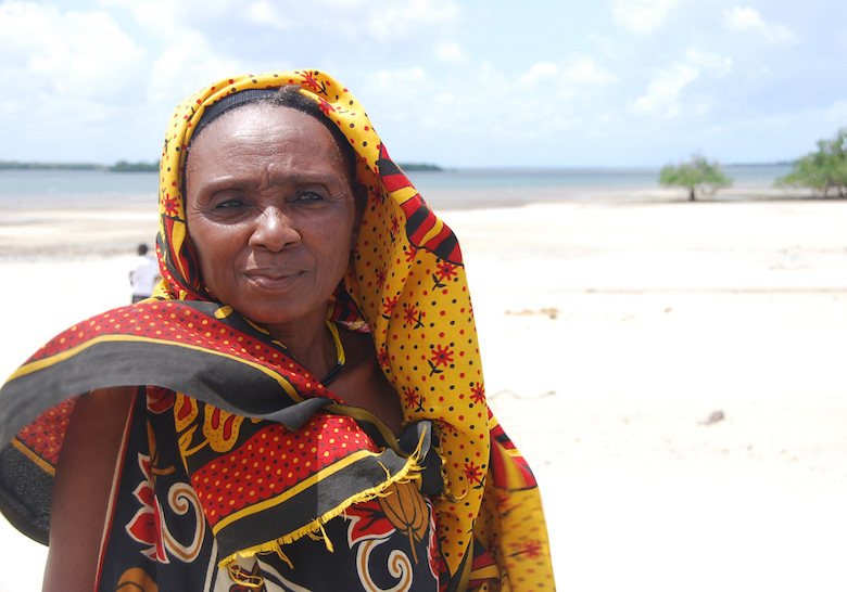 An Aweer woman stands near a mangrove forest and coastline in Lamu, Kenya, that a community conservation project is working to preserve. Photo courtesy of USAID/Flickr.