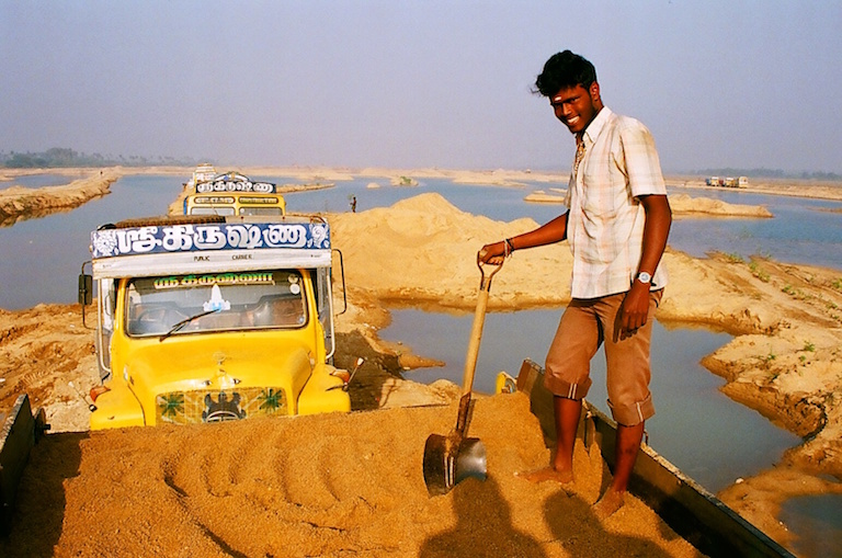 A truck driver loads sand onto his truck in Kanchipuram, Tamil Nadu. Photo by Sibi Arasu.