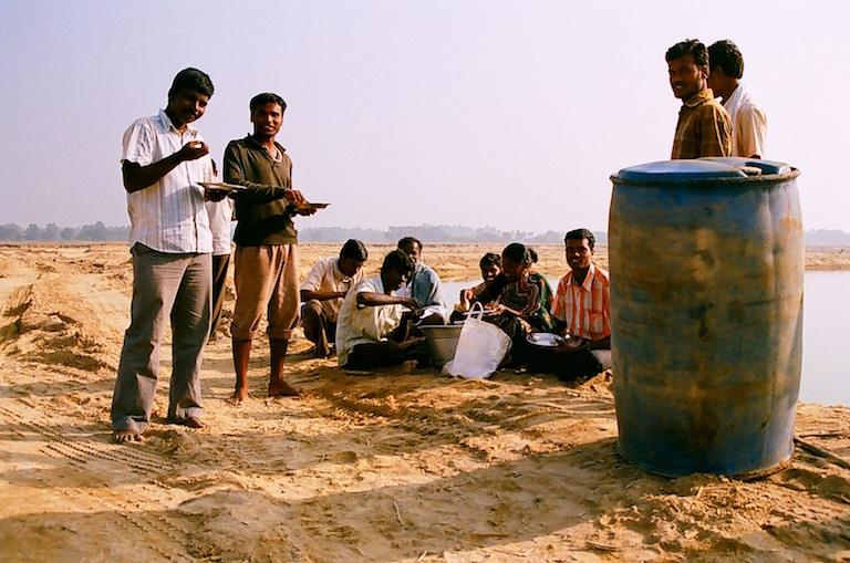 Truck drivers have lunch on the banks of the Palar River while they wait for sand to be loaded in Kanchipuram, Tamil Nadu. It can take up to three days for a truck to reach the front of the queue, load sand, and take off. Photo by Sibi Arasu.