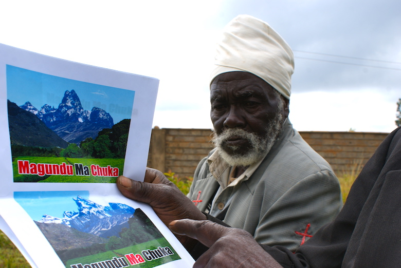 A member of the Atiriri Bururi ma Chuka community group shows a document claiming the right of the community to protect Mt. Kenya forest. Photo by David Njagi.