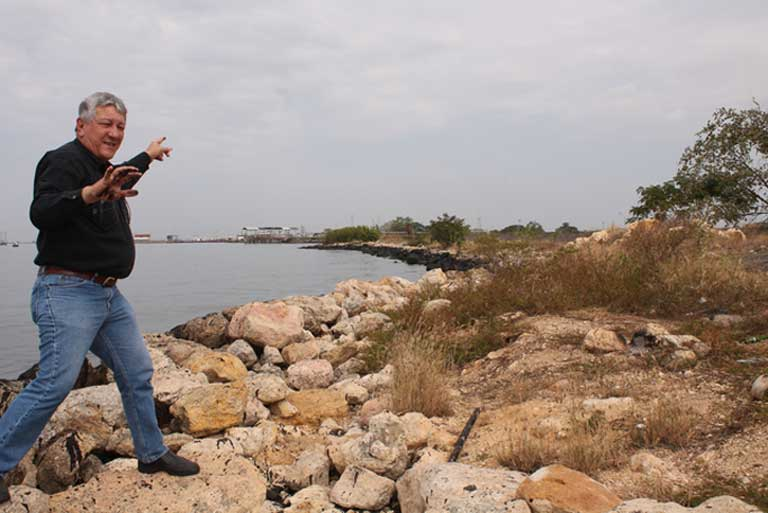 "Alfredo Borges, environmentalist and former PDVSA employee points out oil-blackened rocks at a spot where daily ""micro-spills"" occur in Lagunillas on Lake Maracaibo. Photo by Jeanfreddy Gutiérrez Torres"