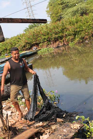A fisherman in a rural village nearby Lagunillas on the east cost of Lake Maracaibo shows an oil stained net, turned black after a single day of use. Photo by María Carlota Marval