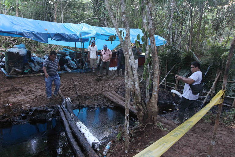 Members of the Marañón Defense Front observe the creek where the oil spilled.  Photo by Barbara Fraser.
